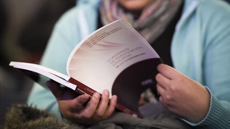 Mujer leyendo un número de Cuadernos de Investigación Educativa